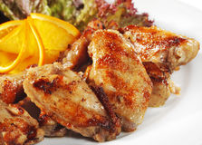 Hot Meat Dishes - Fried Chicken Wings. With Orange Slice and Vegetable Leaf Stock Images