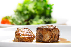 Hot Meat Dishes - Veal Medallions. With Salad on a Background. Selective focus on Meat Stock Photo