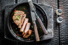 Hot meat with fresh herbs ready to eat. On burnt table Stock Photo