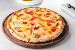 Hot meat Pizza with hamon, cheese and cherry tomatos on the wooden board on the served restaurant table Stock Image