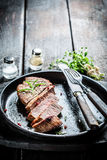 Hot meat with rosemary and papper ready to eat. On burnt table Royalty Free Stock Photos