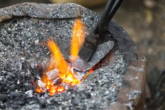 Hot metal arrow blade in the fire. Before being hammered by a blacksmith Stock Photography