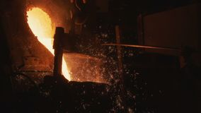 Hot metal pours out of bucket in steel making shop. Close view orange hot metal pours out of converter bucket in factory steel making workshop stock video