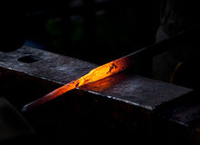 Hot metal rod on an anvil royalty free stock images