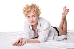 Hot middle aged blonde posing lying on bed Stock Images