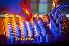Hot Mix. Close-up of audio mixing desk. Motion blurred hand on distant controls. Selective focus on foreground LEDs Royalty Free Stock Images