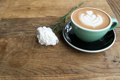 Hot mocha coffee or capuchino in the green cup with heart pattern and white carnation on the wooden table Stock Photo