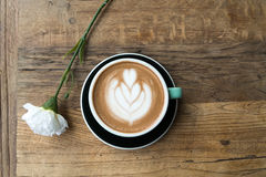 Hot mocha coffee or capuchino in the green cup with heart pattern and white carnation on the wooden table Royalty Free Stock Photo