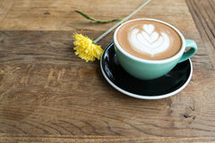 Hot mocha coffee or capuchino in the green cup with heart pattern and yellow flower on the wooden table Royalty Free Stock Images