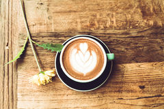 Hot mocha coffee or capuchino in the green cup with heart pattern and yellow flower on the wooden table Royalty Free Stock Photo
