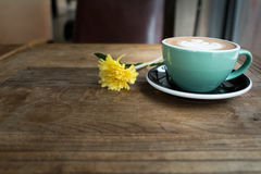 Hot mocha coffee or capuchino in the green cup with heart pattern and yellow flower on the wooden table Stock Photos
