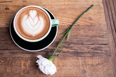 Hot mocha coffee or capuchino with heart pattern and white carnation flower on the wooden table Royalty Free Stock Photography