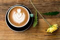 Hot mocha coffee or capuchino with heart pattern and yellow flower and white carnation on the wooden table Royalty Free Stock Images