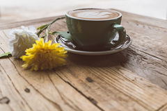 Hot mocha coffee or capuchino with heart pattern and yellow flower on the wooden table Royalty Free Stock Images