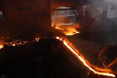 Hot molten iron flowing in the canal in iron factory stock photo