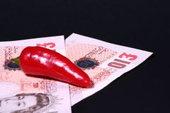 Hot Money. Ten pound notes and a chilli Stock Photography