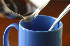 Hot morning coffee being poured in a coffee mug. Pot of coffee being poured into a blue mug. Hot steamy coffee in the glass coffee pot. One spoon in the coffee Stock Photos