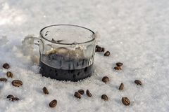 Hot mug of black coffee in cold snow, coffee beans scattered.  Royalty Free Stock Photography
