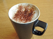 Hot mug of cappuccino coffee Stock Images