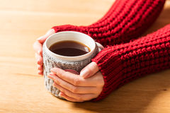 Hot mug of tea warming woman's hands in retro jumper. Stock Images
