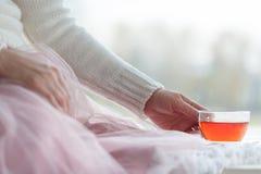 Hot mug of tea with woman hands in retro woollen sweater Stock Photos