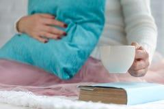 Hot mug of tea with woman hands in retro woollen sweater Stock Images