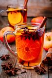 Hot mulled apple cider with cinnamon sticks, cloves and anise. On wooden background stock photography