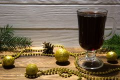 Hot mulled red wine and golden Christmas decorations, sparkling golden balls and beads. Fir tree branches and golden pine cones. royalty free stock photos