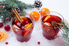 Hot mulled spiced red wine in glass mug with with festive decoration lights and gingerbread Stock Photo