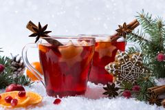 Hot mulled spiced red wine in glass mug with with festive decoration lights and gingerbread Royalty Free Stock Photo