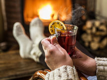 Hot mulled wine and book in woman hands. Relaxing in front of bu Royalty Free Stock Photo