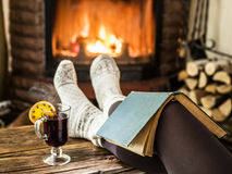 Hot mulled wine and book in woman hands. Royalty Free Stock Photos