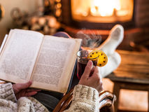 Hot mulled wine and book in woman hands. Royalty Free Stock Photo