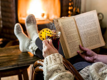 Hot mulled wine and book in woman hands. Royalty Free Stock Images