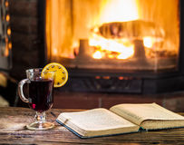 Hot mulled wine and a book on the wooden table. Royalty Free Stock Images