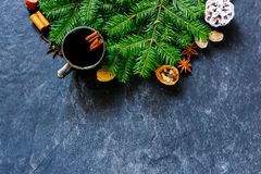 Hot mulled wine. Christmas or New Year hot drink. Holiday mulled wine in rustic mug with spices, ingredients and fir branches over black slate stone background royalty free stock photography