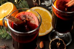 Hot mulled wine with cinnamon and orange in glass cups close-up and Christmas decorations on a dark background. Christmas. new Yea royalty free stock image