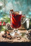 Hot mulled wine. Drink with lemon, apple, cinnamon, anise and other spices in a glass cup between fir tree branches on wooden cutting board stock images