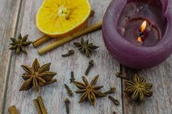 Hot mulled wine drink with lemon, apple, cinnamon, anise and other spices in a glass cup between fir tree branches on wooden. Cutting board. Copy space stock images