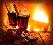 Hot mulled wine on fireplace background - winter warming drink. Hot mulled wine in a glass with orange slices, anise and cinnamon sticks on vintage wood table royalty free stock images