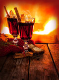 Hot mulled wine on fireplace background - winter warming drink. Hot mulled wine in a glass with orange slices, anise and cinnamon sticks on vintage wood table stock photo