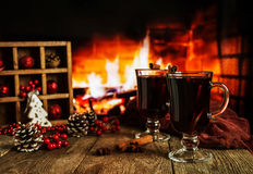Hot mulled wine. In a glass with orange slices, anise and cinnamon sticks on vintage wood table. Fireplace as background. Christmas or winter warming drink Royalty Free Stock Photo