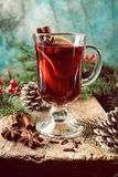 Hot mulled wine. Drink with lemon, apple, cinnamon, anise and other spices in a glass cup between fir tree branches on wooden cutting board stock photography