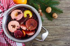 Hot mulled wine in a large pan on a wooden table. Fragrant traditional winter drink. Based on wine, juice, spices, seasonings, fruits. Top view royalty free stock photo