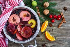 Hot mulled wine in a large pan on a wooden table. Fragrant traditional winter drink. Based on wine, juice, spices, seasonings, fruits. Top view royalty free stock images
