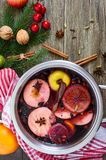 Hot mulled wine in a large pan on a wooden table. Fragrant traditional winter drink. Based on wine, juice, spices, seasonings, fruits. Top view stock image
