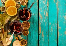Hot mulled wine with orange, cinnamon, cardamom and anise on gre. En wooden background. Top view Royalty Free Stock Images