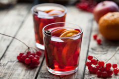 Hot mulled wine or sangria with spices, orange and berries on an old wooden background, selective focus Royalty Free Stock Images