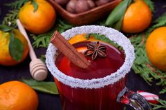 Hot mulled wine with slices of citrus fruits, cinnamon and anise in an Irish glass. Decorated with sugar border royalty free stock photography