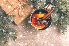 Hot mulled wine in a small vintage pan. With christmas tree on the gray slate background with snowy effect Christmas or winter warming drink. Top view. Copy royalty free stock photo